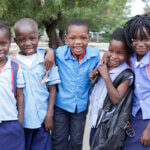 Füünf Kinder in blauen Hemden mit Rucksack am Rücken stehen lachend vor der Kamera.