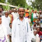 Ein Arzt aus Äthiopien in einem weißen Kittel steht in einer Menschenmenge und lächelt in die Kamera.