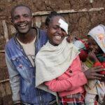 Ein junges Paar mit ihrem kleinen Kind steht vor einem Lehmhaus und lächelt in die Kamera. Die junge Frau in einer rosa Jacke trägt eine Augenbinde und lächelt glücklich. Auch der Partner und das Kind wirken glücklich.