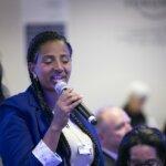 Yetnebersh Nigussie spricht auf einer Konferenz in ein Mikrofon. Sie trägt einen blauen Blazer und ein weißes T-Shirt.