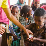 Ein Bub aus Äthiopien hält beide Hände auf, um pinke Pillen gegen die infektiöse Augenkrankheit Trachom zu bekommen. Hinter ihm stehen andere Kinder und warten in der Schlange.
