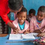 Ein Kind mit Behinderung sitzt lachend neben seinen Klassenkameradinnen. Sie tragen alle einen rosa Pulli. Die Lehrerin beugt sich über das Kind und hält seine Hand, während es in dem Heft vor ihm zu schreiben versucht.