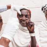 Eine Frau in ein weißes Tuch gehüllt, hält bei einer Augenuntersuchung lachend den Finger in die Höhe, der ihr gezeigt wird.
