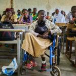 Eine junge Frau im Rollstuhl sitzt in ihrer Klasse und hört wie ihre KameradInnen der LeherIn zu. Sie trägt einen beigen Rock und eine beige-schwarze Zippjacke.