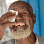 Ein älterer Herr mit weißem Bart drückt ein weißes Tuch auf sein frisch operiertes Auge. Er lächelt breit in die Kamera.