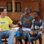 Der österreichische Arzt Philip Überbacher gibt einer Frau aus Mosambik einen Handschlag. Beide lachen.