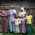 Eine sechsköpfige Familie steht zusammen. Die drei erwachsenen Frauen tragen lange Kleider und schauen sich glücklich an. Eine von ihnen trägt eine Augenbinde von ihrer vergangenen Operation.