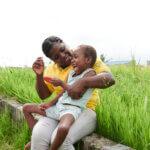 Eine Mitarbeiterin von Licht für die Welt sitzt mit einem Mädchen mit Behinderung vor einer grünen Wiese und lächelt sie an. Das Mädchen hält ein Spielzeug in der Hand und lacht.