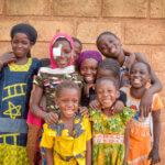 Eine Gruppe von Mädchen in unterschiedlichem Alter steht vor einer Backsteinmauer und lächelt in die Kamera. Alle tragen bunte Kleidung.