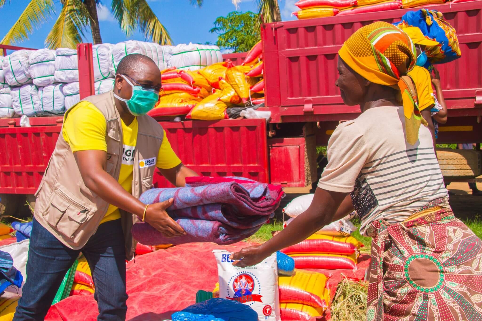 Ein Mitarbeiter von Licht für die Welt übergibt einer Frau Decken und Lebensmittel, nachdem der Zyklon Eloise Mosambik verwüstet hat.