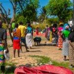 Zahlreiche Menschen mit bunten Kleidern stehen in zwei Reihen an und warten auf die Lebensmittelverteilung von Licht für die Welt. Neben ihnen steht ein großer Lastwagen mit Hilfsgütern.
