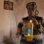 Teresiah hält lächelnd eine Flasche der Seife in die Kamera, die in ihrer Selbsthilfegruppe hergestellt wird.