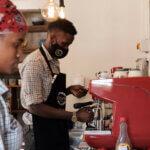 Im Endiro Café wird in Gebärdensprache kommuniziert. Ein junger Mann mit Mundschutz steht vor einer roten Kaffeemaschine und bereitet frischen Kaffee zu.