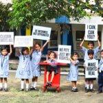Viele Kinder in blauen Schuluniformen mit und ohne Behinderung stehen nebeneinander und halten verschiedene Schilder hoch, die auf ihre Rechte und Gleichberechtigung aufmerksam machen.