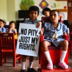 Zwei Kinder mit Behinderung blicken in die Kamera. Einer hält ein Schild mit der Aufschrift: