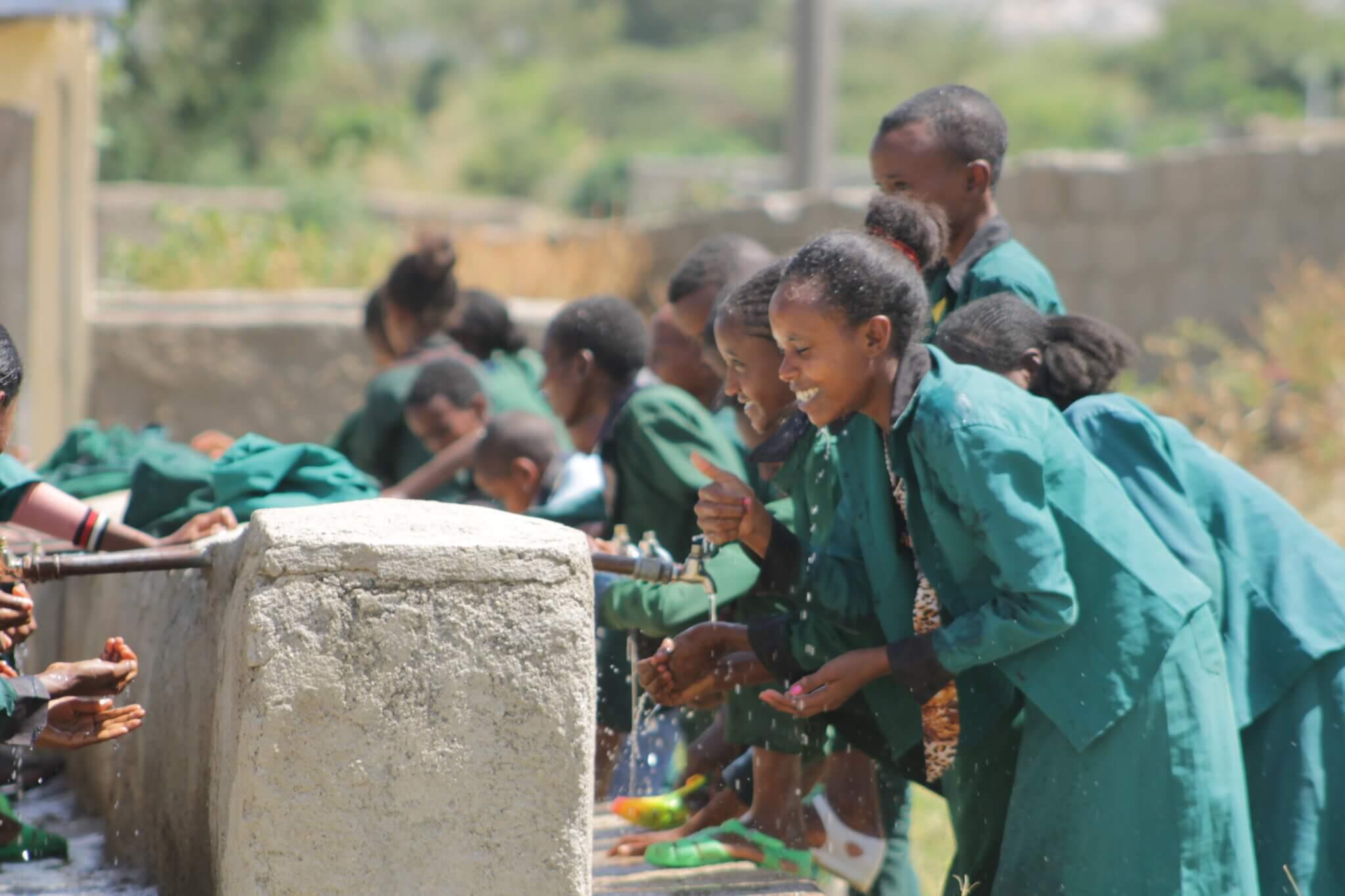Mädchen aus Äthiopien stehen in grünen Schuluniformen vor Brunnen und waschen sich die Hände.
