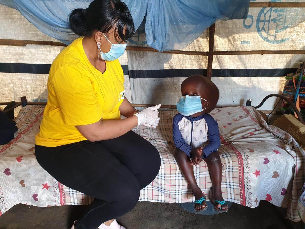 Licht für die Welt Mitarbeiterin Sophia Mohamed sitzt im Flüchtlingslager im Südsudan neben einem kleinen Mädchen auf dem Bett. Das Mädchen hat Hydrozephalus und wird von Licht für die Welt unterstützt.