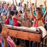 In einer Schulklasse sitzen alle Kinder in Holzbänken hintereinander und heben freudig die Hände.