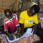 Ein Licht für die Welt Mitarbeiter hilft dem jungen Jima John aus dem Südsudan bei seinen Hausaufgaben. Licht für die Welt betreut im Flüchtlingslager Mahad Menschen mit Behinderungen.
