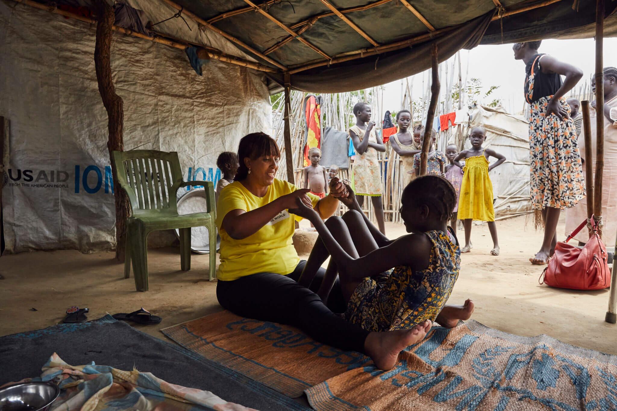 Mitarbeiterin Sophia Mohammed sitzt im Flüchtlingslager im Südsudan am Boden und hilft einem Mädchen bei ihren Rehabilitationsübungen.