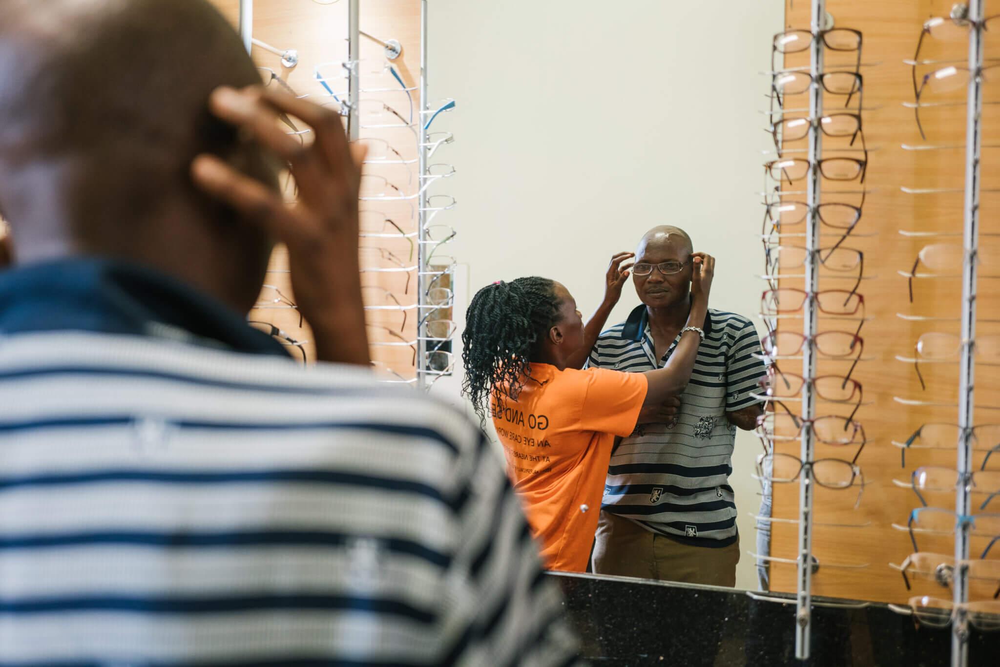 Eine Frau setzt einem Mann beim Optiker eine Brille auf. Der Mann blickt in den Spiegel.