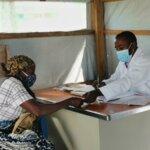 Eine Frau mit Mundschutz sitzt vor einem großen Schreibtisch. Der Arzt in einem weißen Kittel dahinter übergibt ihr etwas, während er einen Stift in der Hand hält.
