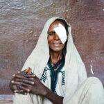 Eine ältere Frau, die gerade operiert wurde, sitzt lächelnd vor einer roten Wand und blickt direkt in die Kamera. Sie trägt beige Leinengkleidung mit dunkelgrünen Ornamenten.