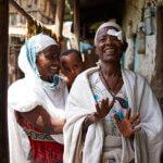 Eine Frau aus Äthiopien lächelt in die Kamera. Sie trägt einen weißen Umhang und hat eine Augenbinde am rechten Auge. Hinter ihr steht ihre Tochter mit dem Enkelkind im Arm.