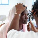 Eine ältere Frau mit einem Rosa Kopftuch wird von einer anderen Frau an den Augen untersucht.