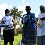 Vier Frauen stehen nebeneinander und packen durchsichtige Gesichtsmasken aus. Sie hatten die Idee, transparente Masken herzustellen, um Menschen, die sich mit Gebärdensprache unterhalten oder Lippen lesen, die Kommunikation zu erleichtern.
