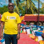 Ein Mitarbeiter von Licht für die Welt steht vor einer roten Planen mit vorbereiteten Hilfsrationen für Menschen, die vom Zyklon Eloise betroffen sind.