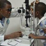 Dr. Abel Polaze blickt durch ein Gerät und untersucht die Augen eines Buben.