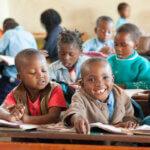 Ein Bub sitzt in der ersten Reihe in der Schule und lächelt über sein Heft hinweg in die Kamera. Er trägt eine beigen Fließjacke und ein blaues Hemd.