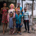 Eine Familie steht vor ihrem Haus und lächelt in die Kamera. Die Mutter, umringt von ihrer Familie, lebt mit Albinismus. Sie hat blonde Haare und trägt ein beige-weißes Kleid.