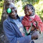 Franciscu aus Mosambik hatte gerade eine Operation am Grauen Star. Er hält seine lachende Enkelin in dne Armen und blickt lachend in die Kamera.
