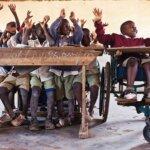 Hinter einer Holzschulbank sitzen viele Kinder und heben die Arme. Sie schauen nach rechts. Daneben sitzt ein Bub in einem Rollstuhl und hebt ebenfalls lachend die Arme.