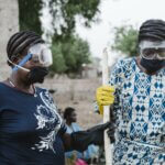Zwei Frauen mit Schutzbrillen, Maske und Gummihandschuhen stehen beieinander und blicken zu Boden. Beide haben dicke Zöpfe um ihre Köpfe geschlungen.