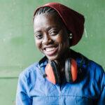 Eine junge Frau mit Lärmschutzkopfhörern um den Hals lächelt in die Kamera. Sie trägt einen blauen Overall und eine rote Mütze. Sie steht vor einem grünen Hintergrund.