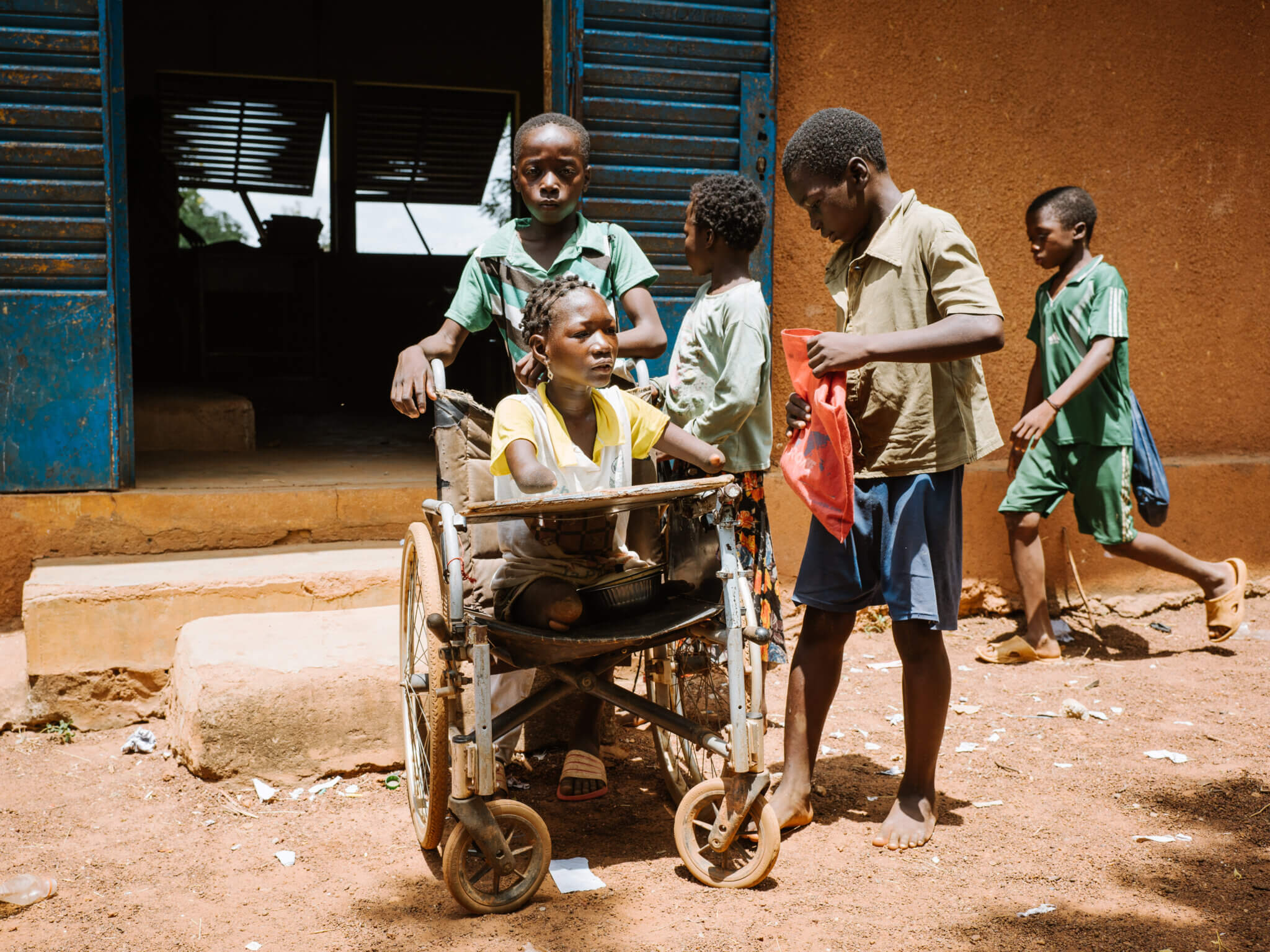 Ein junger Bursch schiebt einen Rollstuhl, indem ein Mädchen mit Behinderung sitzt. Sie trägt goldene Ohrringe, eine weiß-gelbes T-Shirt und blickt in die Weite.