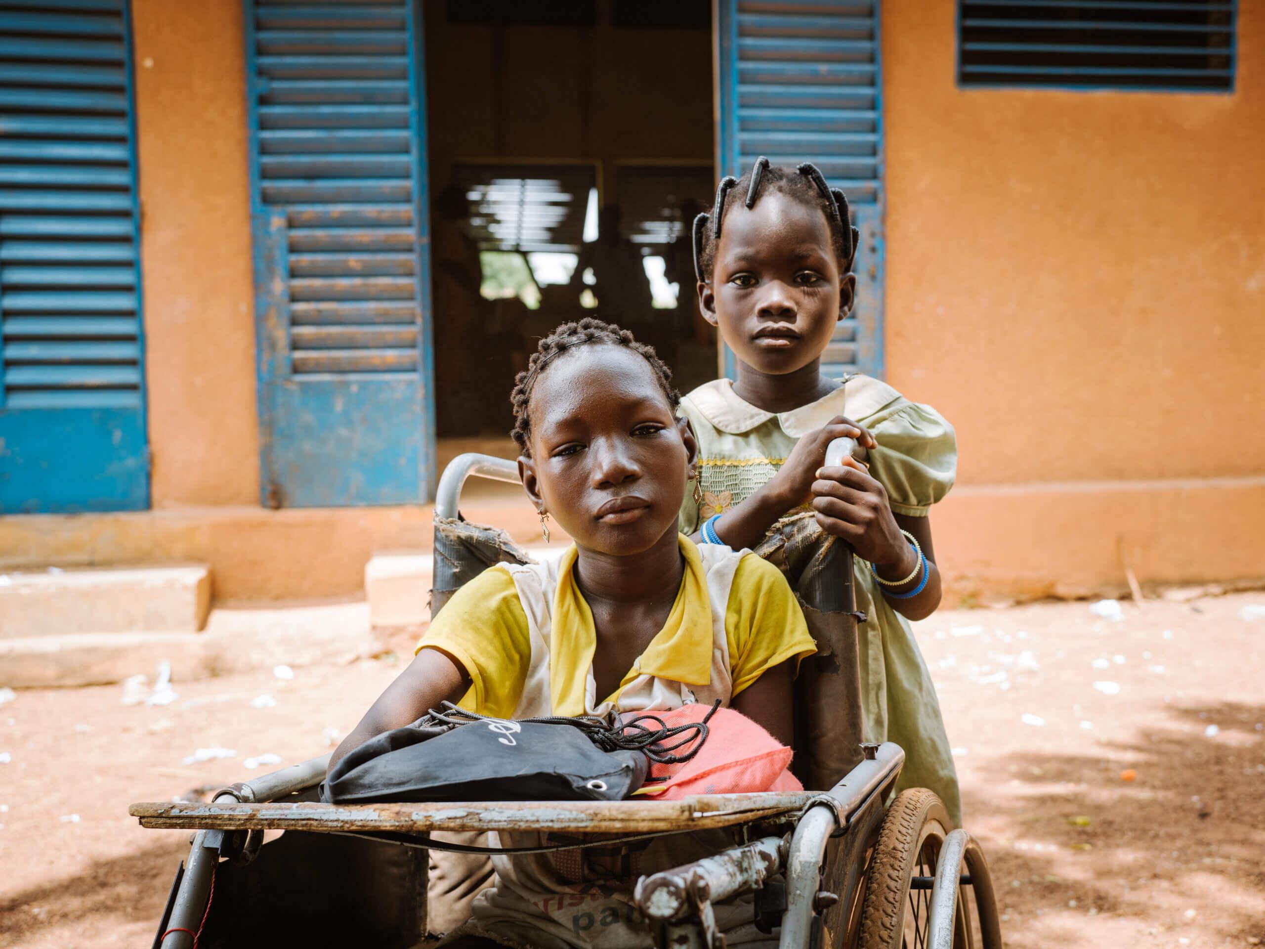 Ein Mädchen mit dicken Zöpfen und einem grünen Kleid mit Kragen schiebt einen Rollstuhl. Sie blickt direkt und ernst in die Kamera. Im Rollstuhl sitzt ein junges Mädchen mit Behinderung. Ihre Arme und Beine sind nicht voll entwickelt. Sie trägt ein gelbes Shirt und goldene Ohrringe. Sie blickt ernst und direkt in die Kamera.