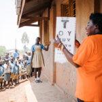 Ein Mädchen in Schuluniform steht mit einigen Metern Entfernung vor einer Frau in einem orangenen T-Shirt, die eine Sehprobentafel hochhält und die Sehkraft des Mädchens prüft. Hinter dem Mädchen steht eine Menge an Kindern, die beide beobachten.