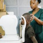 Die Augen eines Buben werden mithilfe eines großen Gerätes untersucht. Eine Frau mit einem grünen Hemd hält den Kopf des Kindes, damit die Augen gut untersucht werden können.
