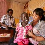 Mitarbeiterin Sophia Mohammed aus dem Südsudan sitzt in dem Schlafzimmer eines Mädchens. Das Mädchen sitzt auf ihrem Schoß und blickt lächelnd in die Kamera. Seine Mutter sitzt hinter den beiden auf dem Bett und hat einen glücklichen Gesichtsausdruck.