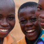 Drei Jugendliche blicken lächelnd in die Kamera. Sie tragen alle ein orangenes Hemd.