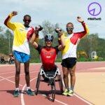Drei Spitzensportler mit Behinderungen stehen am Sportplatz, die Hände jubelnd in die Luft gestreckt und lächeln in die Kamera. Alle tragen ihre Sportbekleidung.