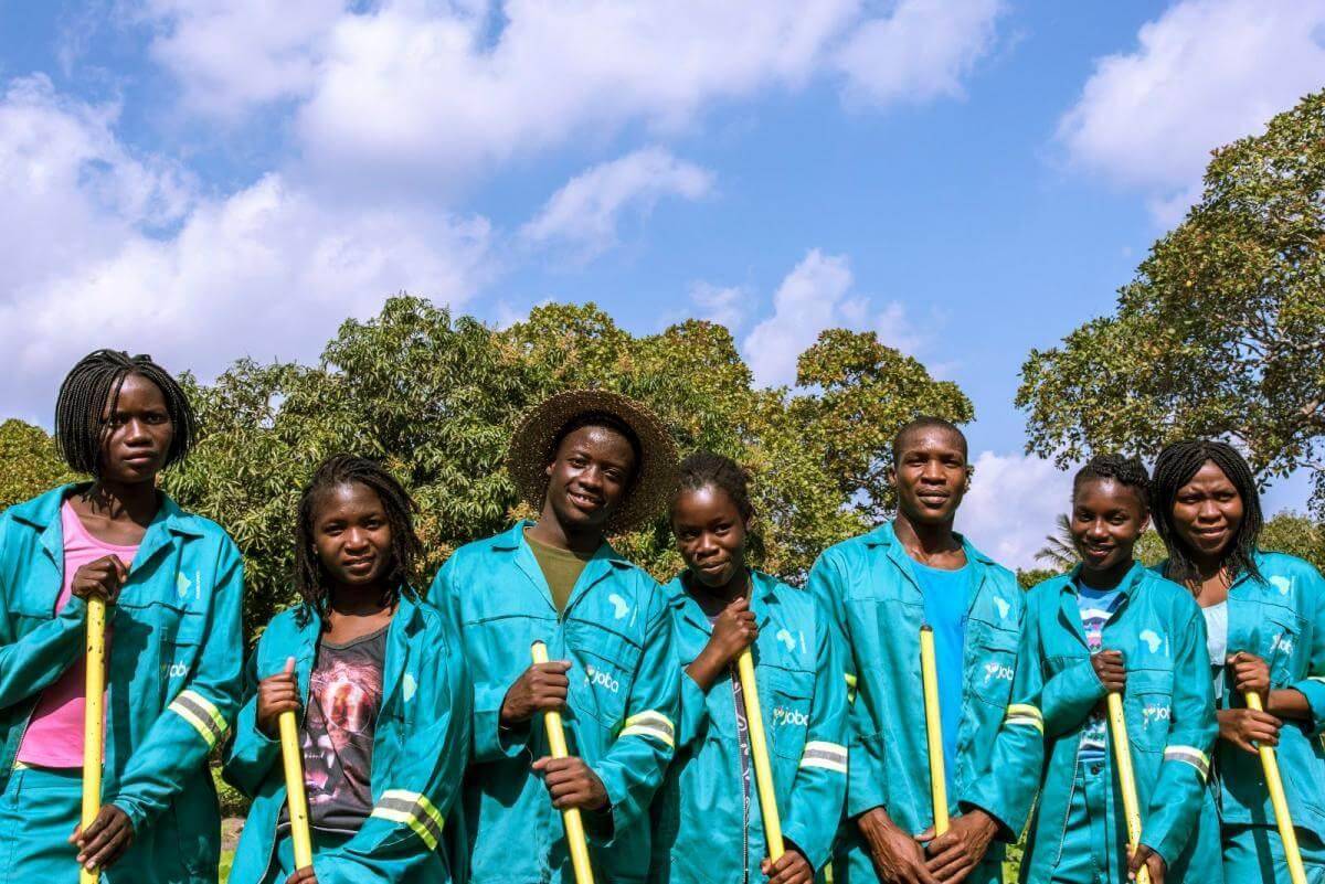 Sieben junge Erwachsene in türkisen Overalls haben einen gelben Besenstiel in der Hand und blicken lächelnd in die Kamera. Hinter ihnen sind Laubbäume und der blaue Himmel zu sehen.