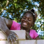 A woman in a pink shirt and a brown cap is working on a brick wall with a big smile in her face.