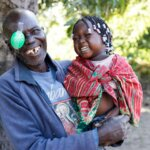 Franciscu from Mozambique has just had cataract surgery. He holds his laughing granddaughter in his arms and looks into the camera.