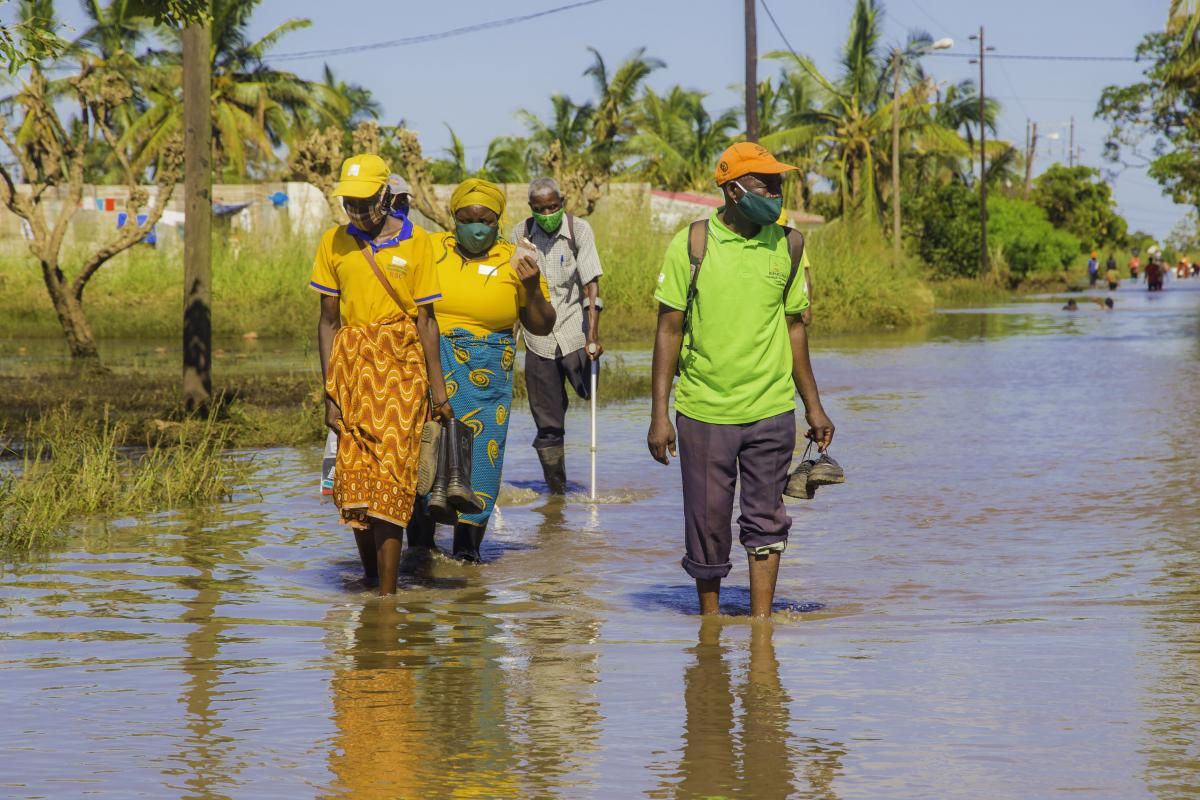 People walk in flooded Buzi after Cyclone Eloise hit