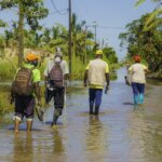 Four people, including Light for the World staff, walk through a muddy environment after another cyclone devastated Mozambique. All are wearing rubber boots and face masks.